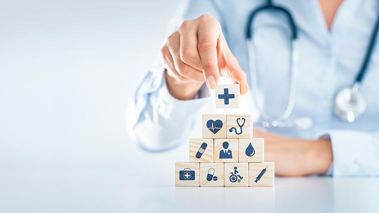 Hand, die Würfel mit medizinischen Motiven stapeltn